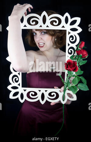 Beautiful woman holding white wooden frame with red roses with her arms wrapped around frame. - Stock Photo