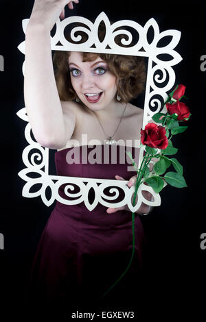Beautiful woman holding white wooden frame with red roses with her arms - Stock Photo