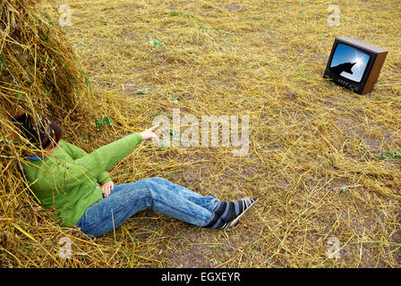 Girl on hay watch tv. Conceptual design. - Stock Photo