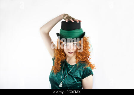 Pretty young Irish woman with long, curly red hair wearing a hat - Stock Photo