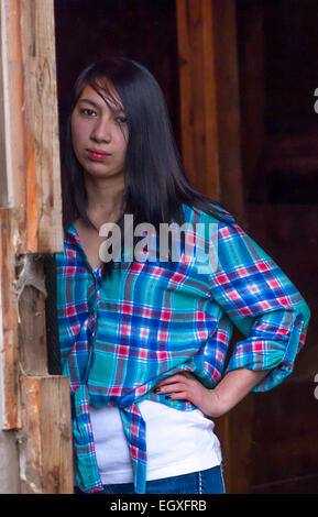 Young woman leans against doorway. - Stock Photo