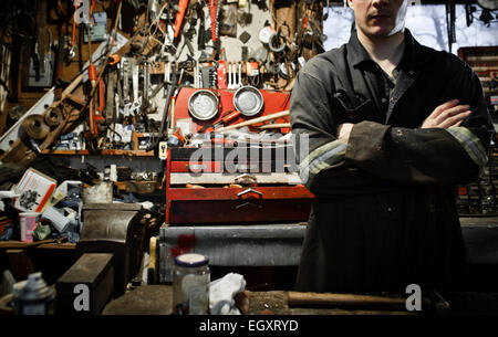 Arm Crossed Worker in a Shed and Lots of Tools Hanging on the Wall - Stock Photo