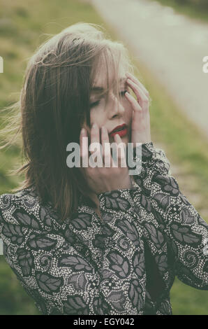 Beautiful young woman head in hands in the countryside - Stock Photo
