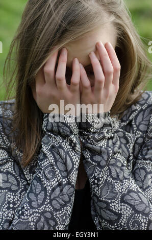 Young woman head in hands crying outdoors - Stock Photo