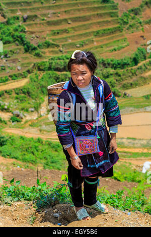 A Hmong woman on the trail in the village of Lao Chai near Sapa, Vietnam, Asia. - Stock Photo