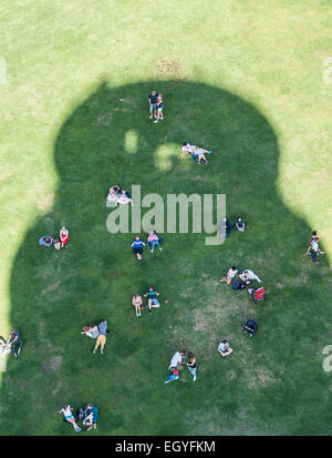 Tourists cooling off in the shade of the Leaning Tower of Pisa, Piazza del Duomo, Piazza dei Miracoli, Pisa, Tuscany, - Stock Photo