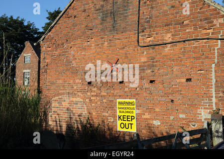 Warning Dangerous Buildings Keep Out sign on building - Stock Photo