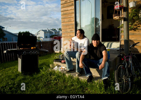 Two young men sit on the back step in Fort McMurray. - Stock Photo