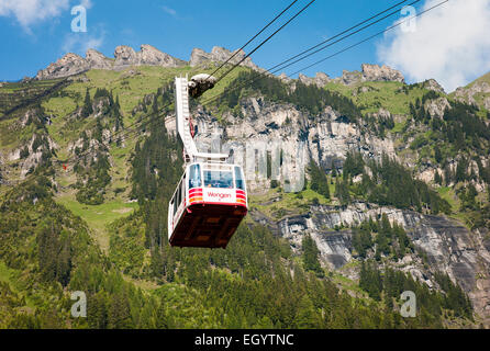 Gondola cable car rising out of Wengen village in Swiss Alps - Stock Photo