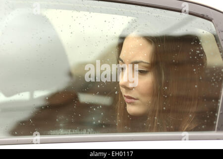 Sad woman looking down through a car window in a rainy day - Stock Photo