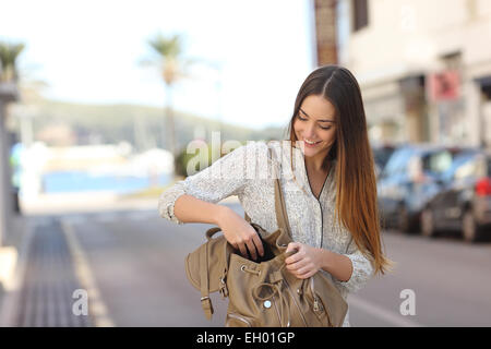 Casual happy woman walking on the street and searching something in a bag - Stock Photo
