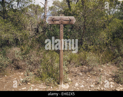Spain, Menorca, signpost with two arrows pointing in opposite directions - Stock Photo