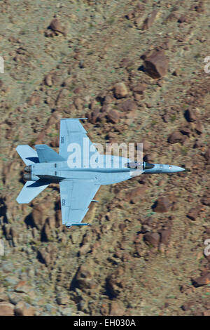 United States Navy F-18 Super Hornet, Flying At Low Level Through A Desert Canyon. - Stock Photo