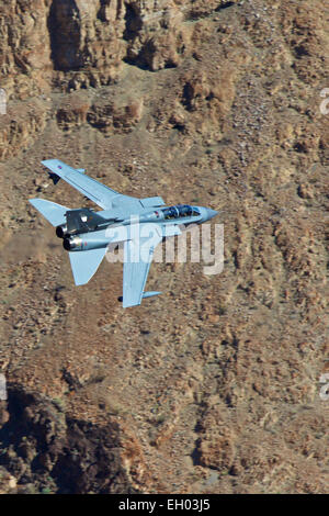 Royal Air Force Tornado GR4 Jet Fighter Flying At Low Level Through A Desert Valley. - Stock Photo