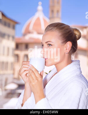 Portrait of a beautiful calm woman drinking coffee in hotel room in Florence, standing on the balcony and enjoy - Stock Photo