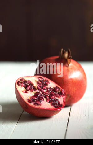 Still life food image of Pomegranates on a white wooden surface - Stock Photo