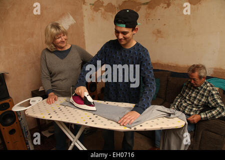 Teenager with grandparents and ironing - model released - Stock Photo
