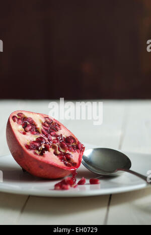 Still life food image of a Pomegranate on a white plate with spoon - Stock Photo