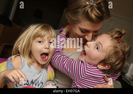 Children making funny faces with mother - model released - Stock Photo