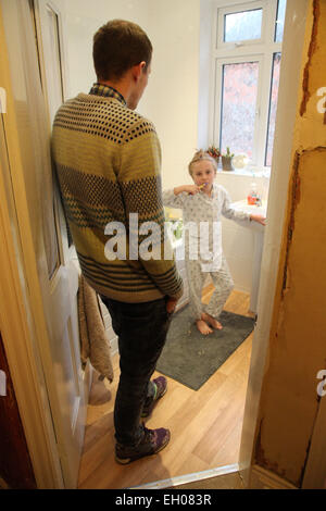 Father watching daughter brushing teeth - model released - Stock Photo
