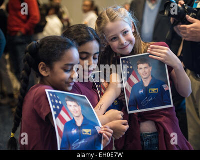 Some students pose with their newly autographed photos of Astronaut Reid Wiseman during his visit to the Maryland - Stock Photo