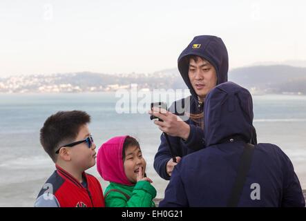 Asian man, using selfie stick, taking selfie photo, Vista Point, north side of Golden Gate Bridge, city of Sausalito, - Stock Photo