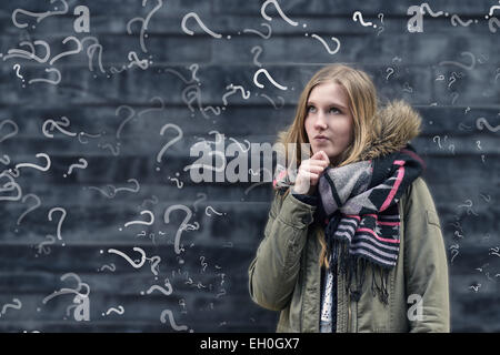 Pretty young female student in class with a problem to solve standing in front of a chalkboard in class covered - Stock Photo
