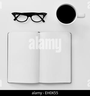 high-angle shot of a blank notebook, a pair of black plastic-rimmed eyeglasses for women and a cup of coffee on - Stock Photo