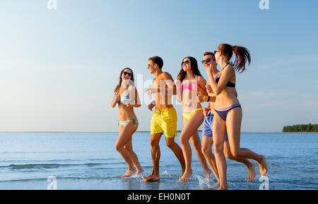 smiling friends in sunglasses running on beach - Stock Photo