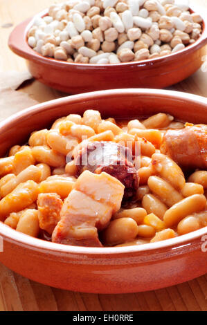 closeup of an earthenware bowl with fabada asturiana, a typical spanish bean stew - Stock Photo