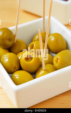 a plate with olives with toothpicks served as tapas on a white background - Stock Photo