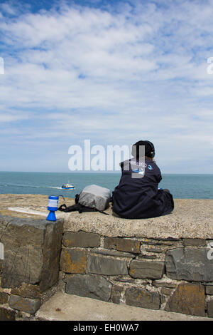A dolphin spotter, an observer from the Seawatch Foundation on the stone pier at New Quay, Ceredigion,  looking - Stock Photo
