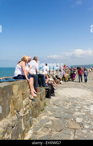 Visitors to New Quay, Ceredigion, enjoying the summer sun on the stone pier overlooking New Quay bay. - Stock Photo