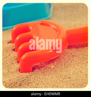 closeup of an orange rake on the sand of a beach or of a sandpit, with a retro effect - Stock Photo