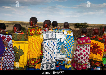 Rear view of Masai Women wearing the traditional shawls called Kangas, in a village near the Masai Mara, East Africa - Stock Photo
