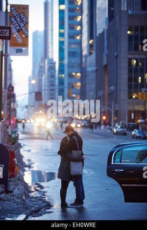 Couple cuddle on 6th Avenue Manhattan in New York North America USA - Stock Photo
