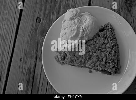 Black and white photograph of a piece of apple pie with ice cream on a plate. - Stock Photo
