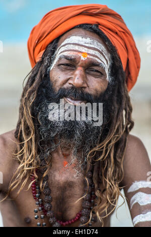 A portrait of a Hindu devotee known as a Sadhu with the characteristic orange head band and dreadlocks in the city - Stock Photo