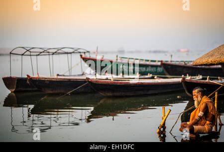A Hindu devotee sitting by the Ganges river in Varanasi, meditating in the sunrise. - Stock Photo
