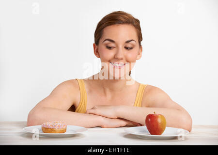 Young Woman Choosing Between Donut And Cake For Snack - Stock Photo