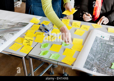 Cropped image of business people strategizing with sticky notes in office - Stock Photo