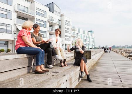 Full length of happy female friends talking on floorboard at seaside - Stock Photo