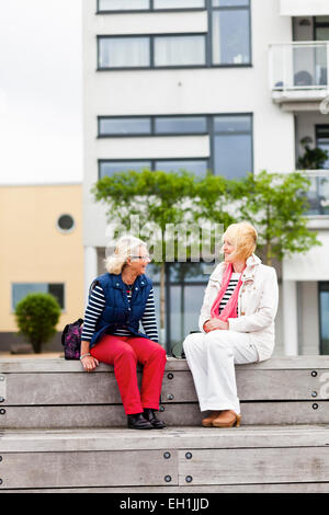 Full length of mature female friends talking on floorboard - Stock Photo