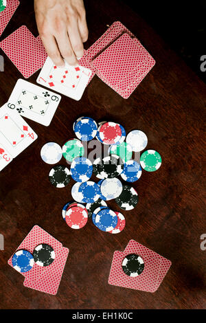 Directly above shot of gambling chips and playing cards on table - Stock Photo