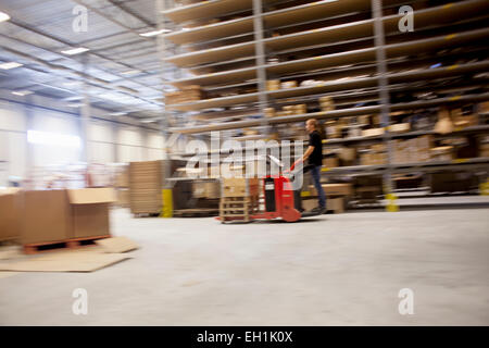 Man driving forklift truck in factory warehouse - Stock Photo