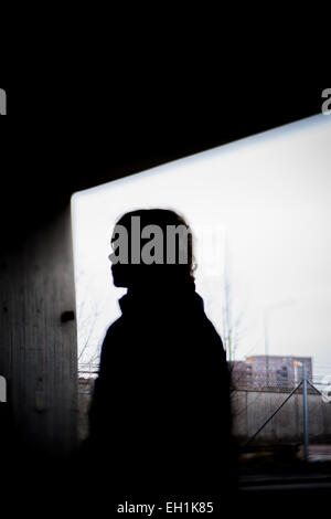Silhouette person standing against window - Stock Photo