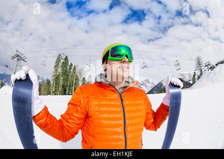 Smiling guy wearing mask holding ski in winter - Stock Photo