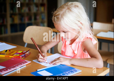 Cute girl drawing during art class - Stock Photo