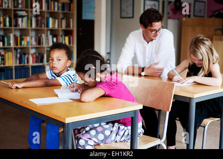 Teacher and students in classroom - Stock Photo