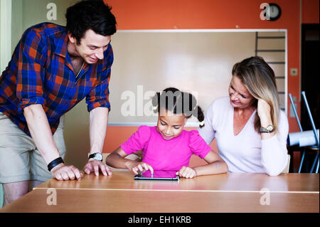 Teachers with girl painting on tablet computer in classroom - Stock Photo